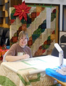 Note the wonderful quilted Pointsettia over Tricia's shoulder.  That's Annie's project on the wall behind