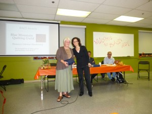 BMQG President Wendy Lynn accepts the award from BACI Co-Executive Director Tanya Sather